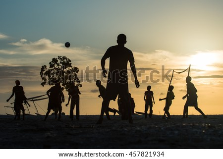 Editorial use. Even facing hard life conditions, people in Africa are optimistic and joyful. Image of young men playing on the beach of Nungwi village in Zanzibar Island at sunset, April 2016
