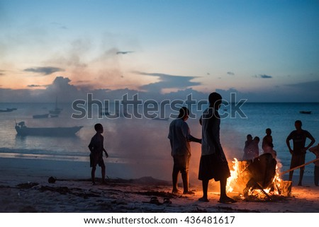 Editorial use. Fishermen in Zanzibar dry their boats at sunset each day. They use controlled fire and all the community participates in the process. Image taken in Nungwi village, April 2016.