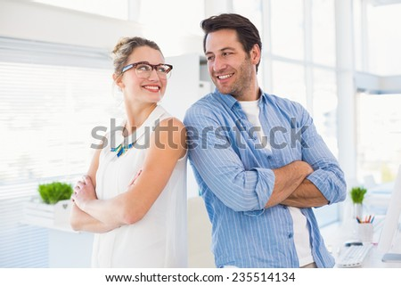 Editors posing with arms crossed looking at each other in office - stock photo