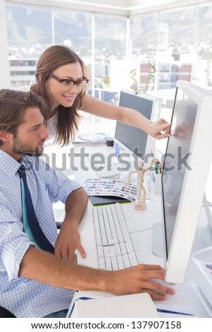 Editors reviewing photographs on computer at their desk in bright office - stock photo