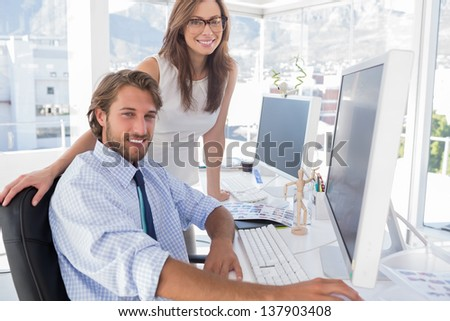 Editors smiling at the camera at their desk in modern office - stock photo