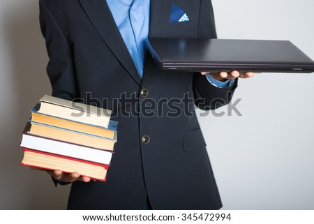 Education - a choice between books and laptop, without a face. advertising or business concept, isolated on a gray background.