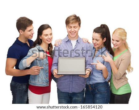 education, advertisement and new technology concept - smiling students with laptop computer blank screen