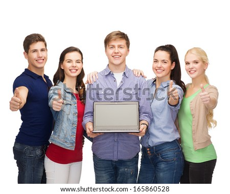 education, advertisement and new technology concept - smiling students with laptop computer blank screen showing thumbs up - stock photo