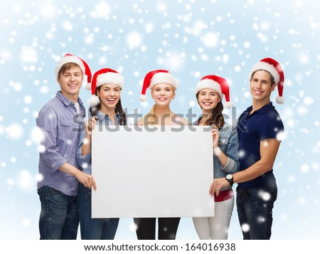 education, advertisement, sale, christmas and people concept - group of smiling students in santa helper hats with blank white board - stock photo