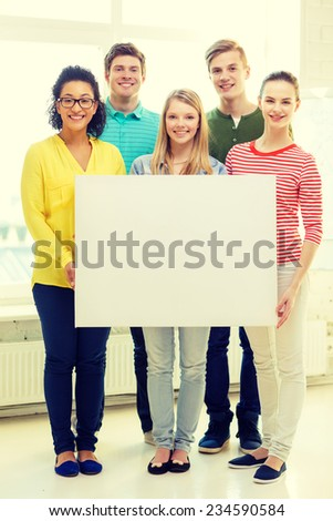 education, advertising and school concept - five smiling students with white blank board at school - stock photo