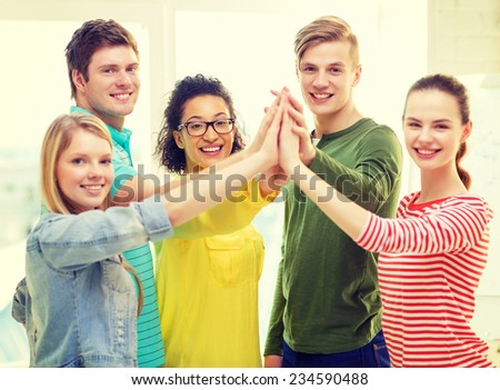 education and friendship concept - five smiling students giving high five at school - stock photo
