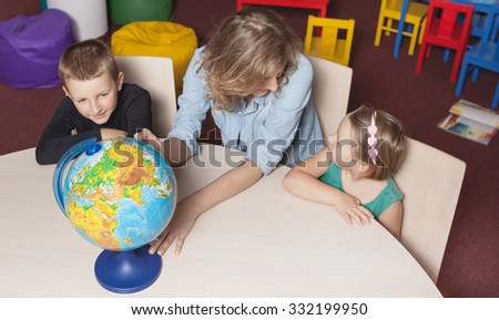 Education and fun. Globe. Kids with teacher in classroom scenery. Portrait of couple of kids in classroom, playing and educating