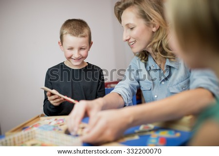 Education and fun. Kids with teacher playing games in classroom scenery. Portrait of couple of kids in classroom, playing and educating