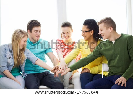 education and happiness concept - smiling students at school with hands on top of each