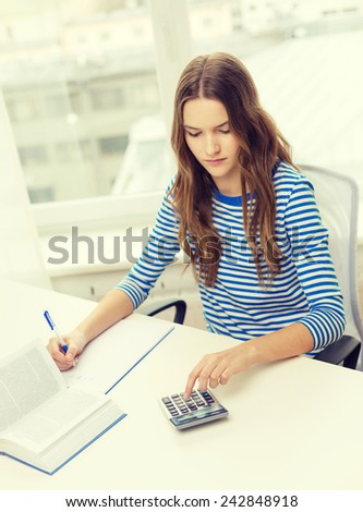 education and home concept - concentrated student girl with notebook, calculator and book - stock photo
