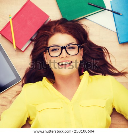 education and home concept - smiling redhead female student in eyeglasses lying on floor - stock photo