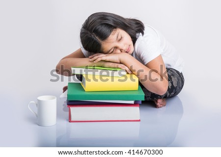 education and home concept - stressed student girl with books, indian girl child tired of studying or doing homework, asian girl stressed with studies, sitting over white floor - stock photo