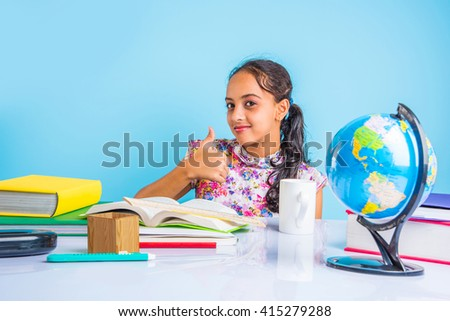 education and home concept - stressed student girl with books, indian girl child tired of studying or doing homework, asian girl studying and stressed, with globe toy and coffee mug  - stock photo