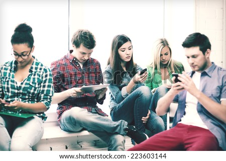 education and internet concept - students looking at their phones and tablet pc at school - stock photo
