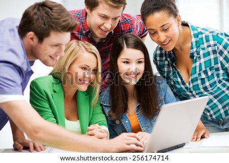education and internet - smiling students looking at tablet pc in lecture at school - stock photo