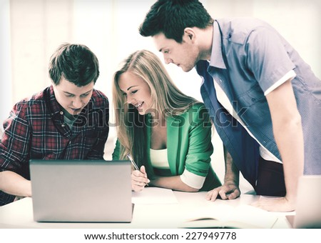 education and internet - smiling students writing test or exam in lecture at school - stock photo