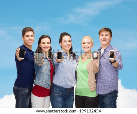education and modern technology concept - smiling students showing blank smartphones screens over blue sky background