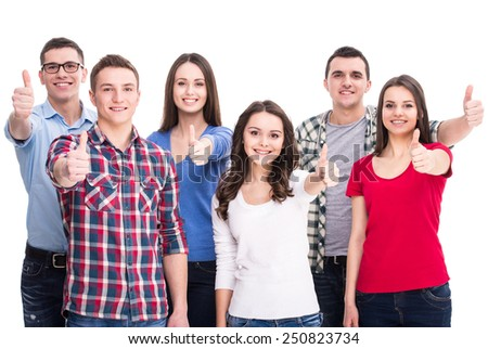 Education and people concept. Group of smiling students are standing and showing thumbs up. - stock photo