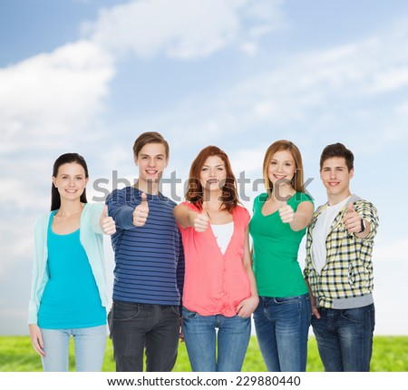 education and people concept - group of smiling students standing and showing thumbs up - stock photo