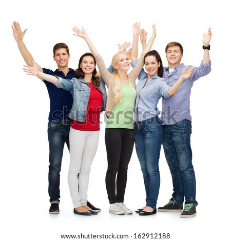 education and people concept - group of smiling students standing and waving hands - stock photo