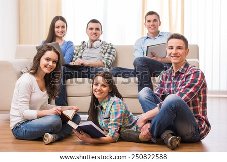 Education and people concept. Group of students with books, and laptop are looking at the camera while resting in room. - stock photo
