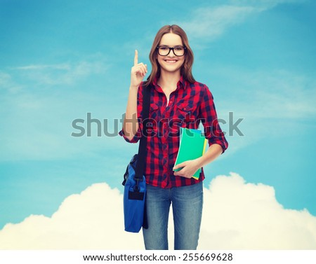education and people concept - smiling female student in eyeglasses with bag and notebooks showing finger up over blue sky background - stock photo