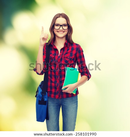 education and people concept - smiling female student in eyeglasses with bag and notebooks showing finger up over green background - stock photo