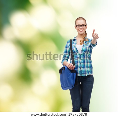 education and people concept - smiling female student in eyeglasses with laptop bag showing thumbs up over green background - stock photo