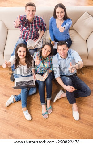 Education and people concept. Top view of group of students are sitting on sofa and on the floor with laptop and books. - stock photo