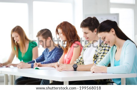 education and school concept - five smiling students with textbooks at school