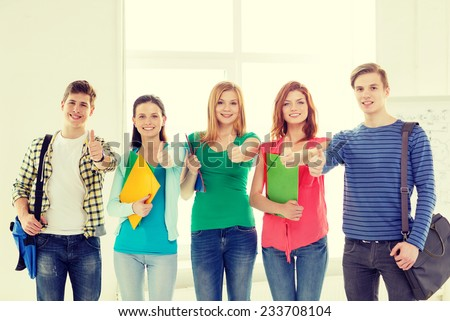 education and school concept - group of smiling students with bags and folders at school showing thumbs up - stock photo