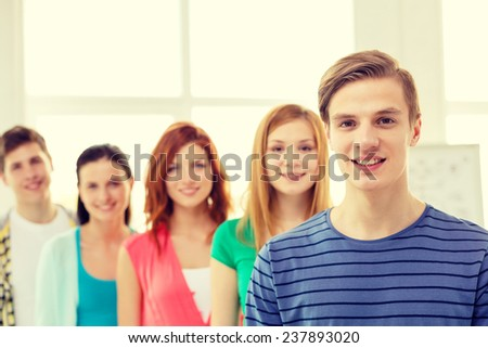 education and school concept - group of smiling students with teenage boy in front - stock photo