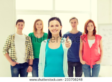 education and school concept - group of smiling students with teenage girl in front showing thumbs up - stock photo