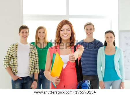 education and school concept - group of smiling students with teenage girl in front with bag and folders showing thumbs up - stock photo