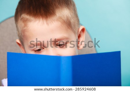Education and school concept. Little boy reading a book, child kid on blue background holding an open book - stock photo