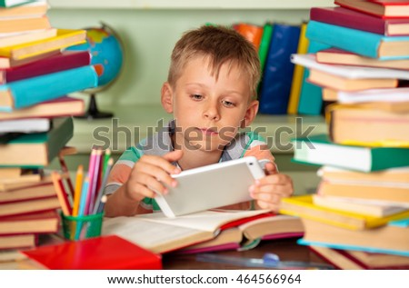 Education and school concept - little schoolboy with tablet  in the library.