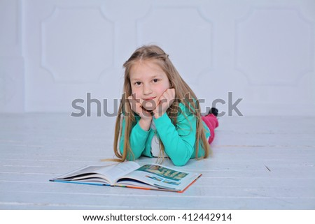 education and school concept - little student girl lying on a floor with a book studying and reading. happy pre-teen girl reading encyclopedia at home - stock photo
