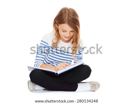education and school concept - little student girl sitting on floor and reading book - stock photo