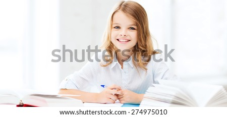education and school concept - little student girl studying at school - stock photo