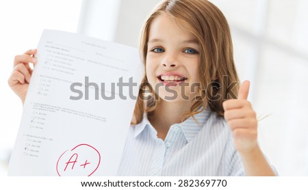 education and school concept - little student girl with test and A grade at school showing thumbs up - stock photo