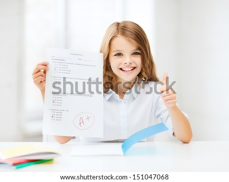 education and school concept - little student girl with test and A grade showing thumbs up at school - stock photo
