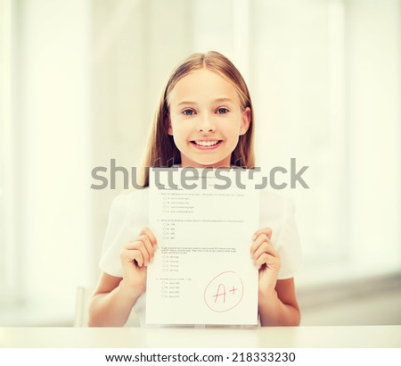 education and school concept - little student girl with test and grade at school - stock photo