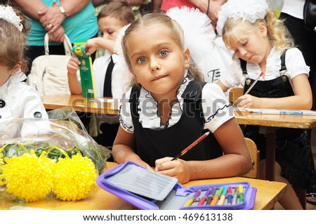 education and school concept - smiling little student girl. Beautiful girl in a school uniform sitting at desk