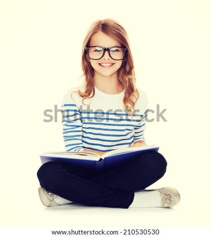 education and school concept - smiling little student girl with book and eyeglasses sitting on the floor - stock photo