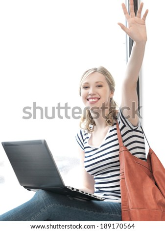 education and technology concept - happy teenage girl waving a greeting with laptop - stock photo