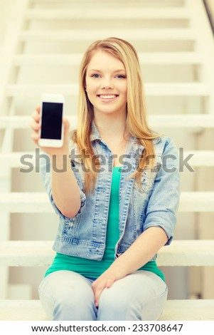education and technology concept - smiling female student showing smartphone blank screen sitting on staircase