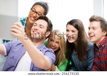 education and technology - group of students taking selfie with tablet pc at school - stock photo