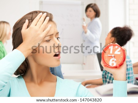 education and time management - attractive student looking at clock - stock photo