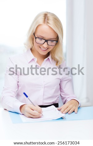 education, business and people concept - smiling businesswoman or student in eyeglasses with documents writing or making tax report in office